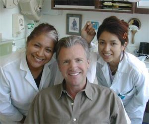 Three people patient in the middle with two female dental office nurses behind